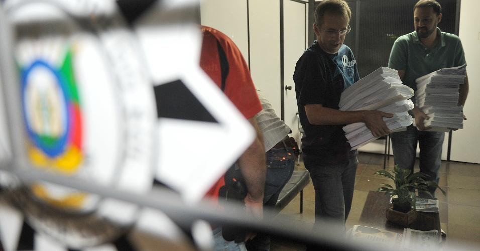 22.mar.2013 - Policiais civis carregam inquérito sobre a investigação do incêndio que matou 241 pessoas na boate Kiss, na 1ª Delegacia de Santa Maria. Na madrugada desta sexta-feira (22), as 10 mil páginas de material foram levadas à Delegacia Regional, em Santa Maria. Devido ao tamanho do relatório final (52 volumes), um comboio de três viaturas levará o material para o Fórum da cidade, na tarde desta sexta-feira (22)