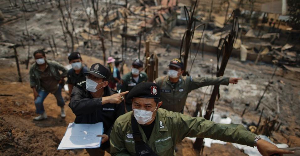 23.mar.2013 - Legistas trabalham em meio aos escombros causados pelo incêndio que atingiu um campo de refugiados birmaneses em Mae Surin, no norte da Tailândia, neste sábado (23). Pelo menos 62 pessoas morreram e mais de 200 ficaram feridas. O local abrigava cerca de 4.000 refugiados. Duzentos dos 281 alojamentos foram destruídos pelo fogo. Informações dão conta de que o fogo teria começado em um incidente na cozinha de um dos alojamentos