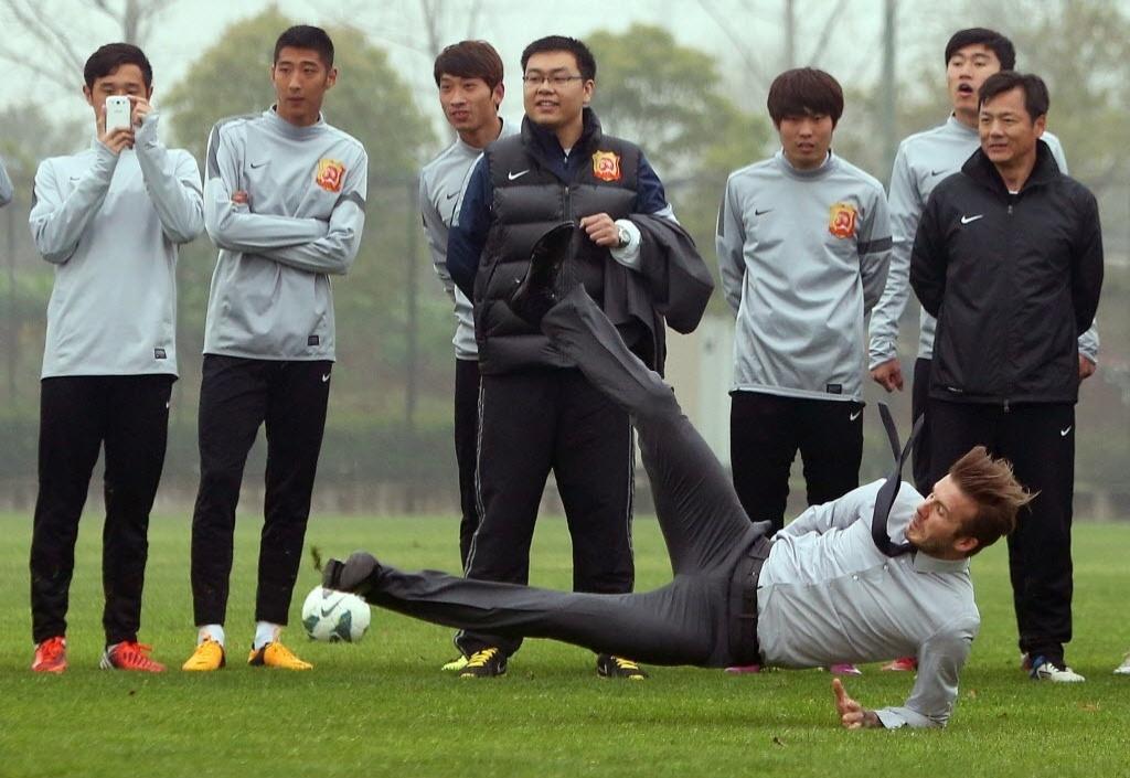 David Beckham escorrega ao tentar chutar a bola e cai no gramado durante evento beneficente em Wuham, na China