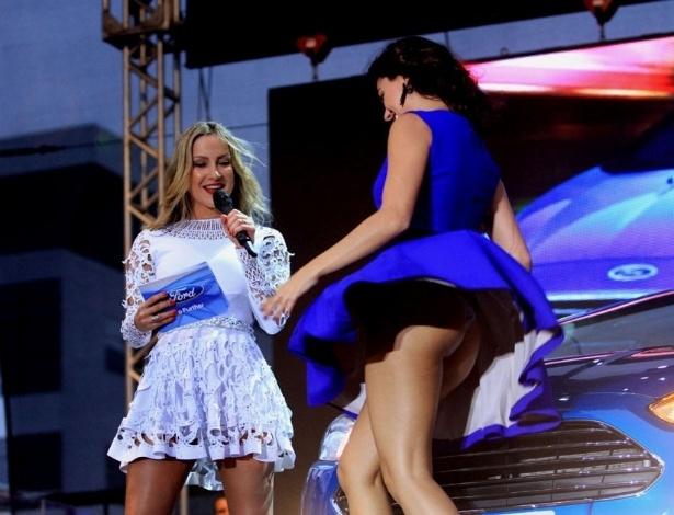 24.mar.2013 - Apresentadora de um evento de uma marca de carros ao lado de Claudia Leitte, Ísis Valverde se atrapalhou com o vento no palco e acabou mostrando demais