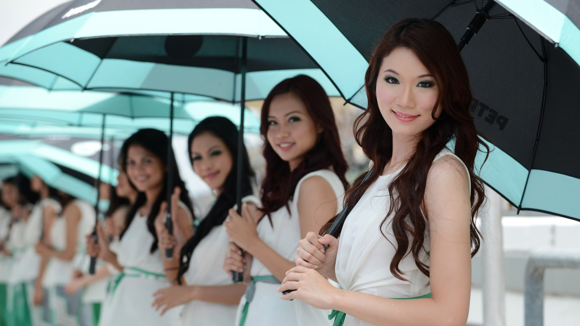 24.mar.2013 - Belas grid girls fazem pose na reta dos boxes do circuito de Sepang