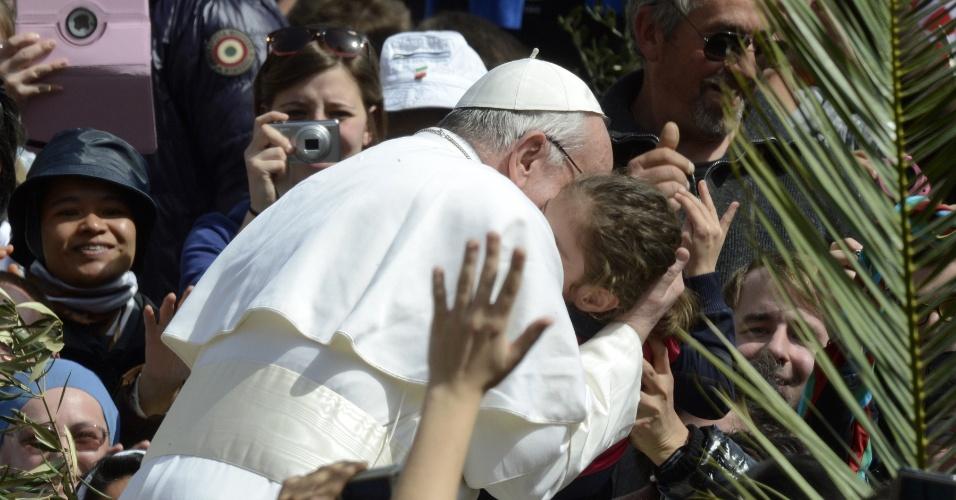24.mar.2013 - Papa Francisco beija mais uma criança entre as centenas de fiéis na praça São Pedro, onde  celebra a tradicional missa do Domingo de Ramos, no Vaticano