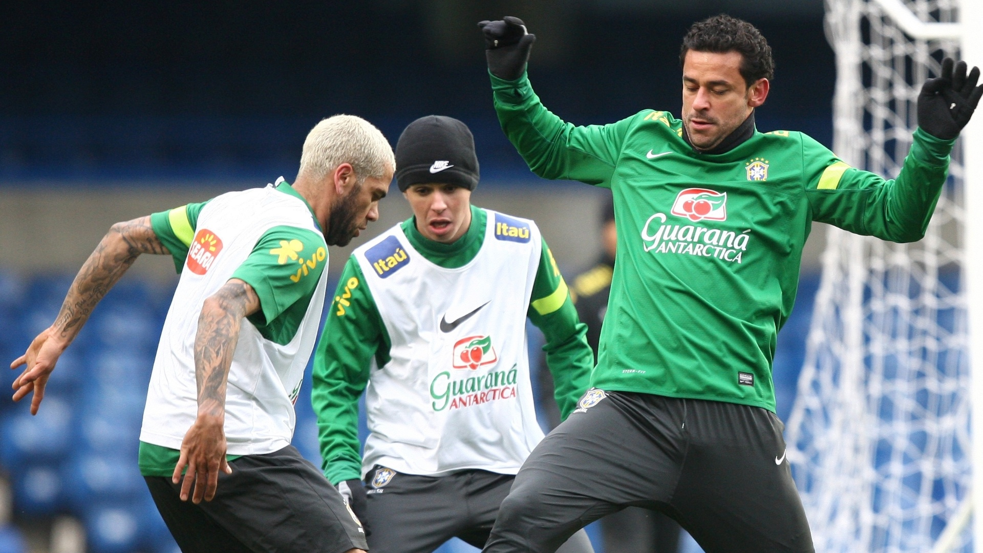 24.mar.2013 - Fred e Daniel Alves disputam a bola durante treinamento da seleo brasileira e so observados por Oscar