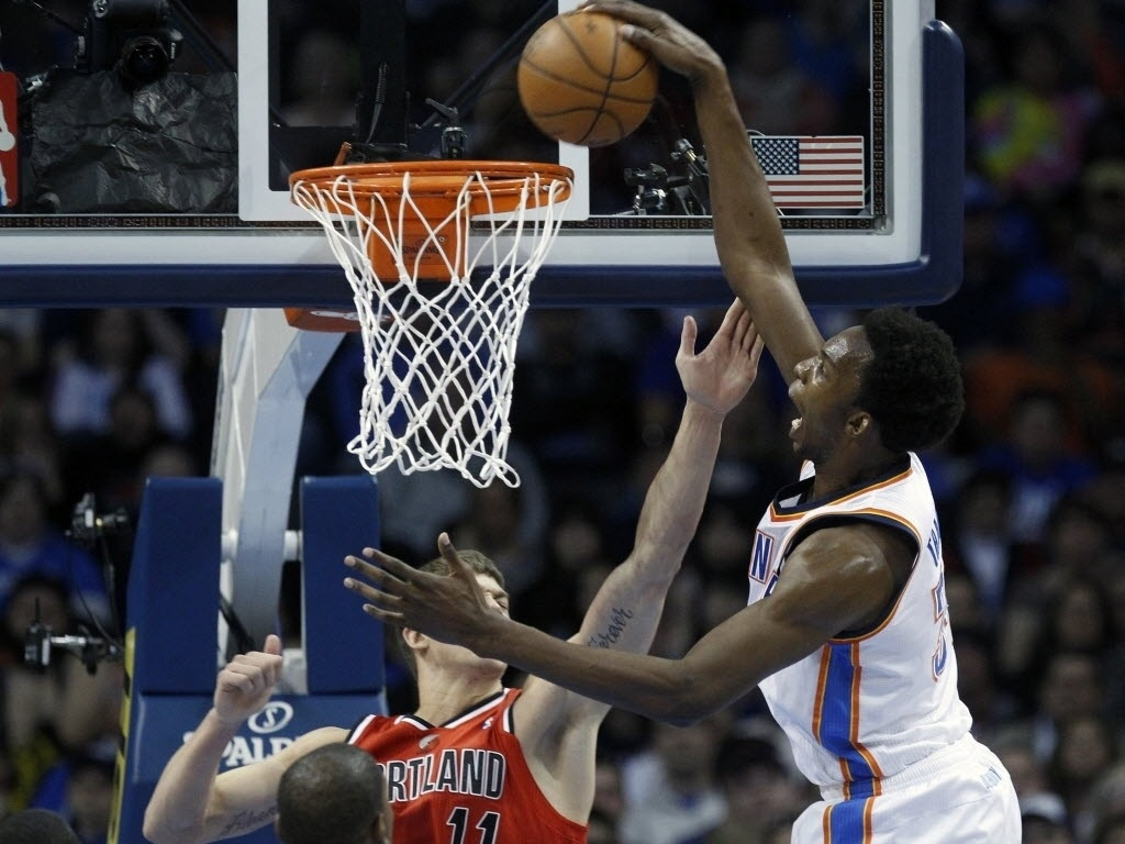 24.mar.2013 - Hasheem Thabeet, do Thunder, sobe para enterrada sobre Meyers Leonard, dos TrailBlazers, durante a vitria da equipe de Oklahoma