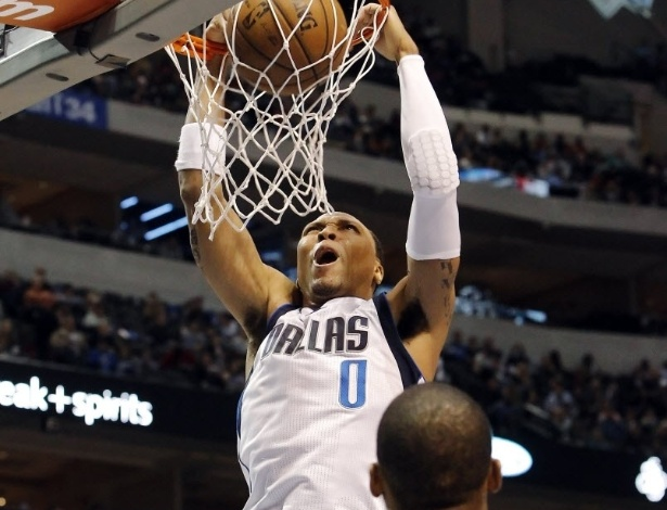 24.mar.2013 - O ala Shawn Marion faz careta enquanto crava sendo observado por Randy foye, do Jazz, na vitória do Dallas Mavericks sobre o rival