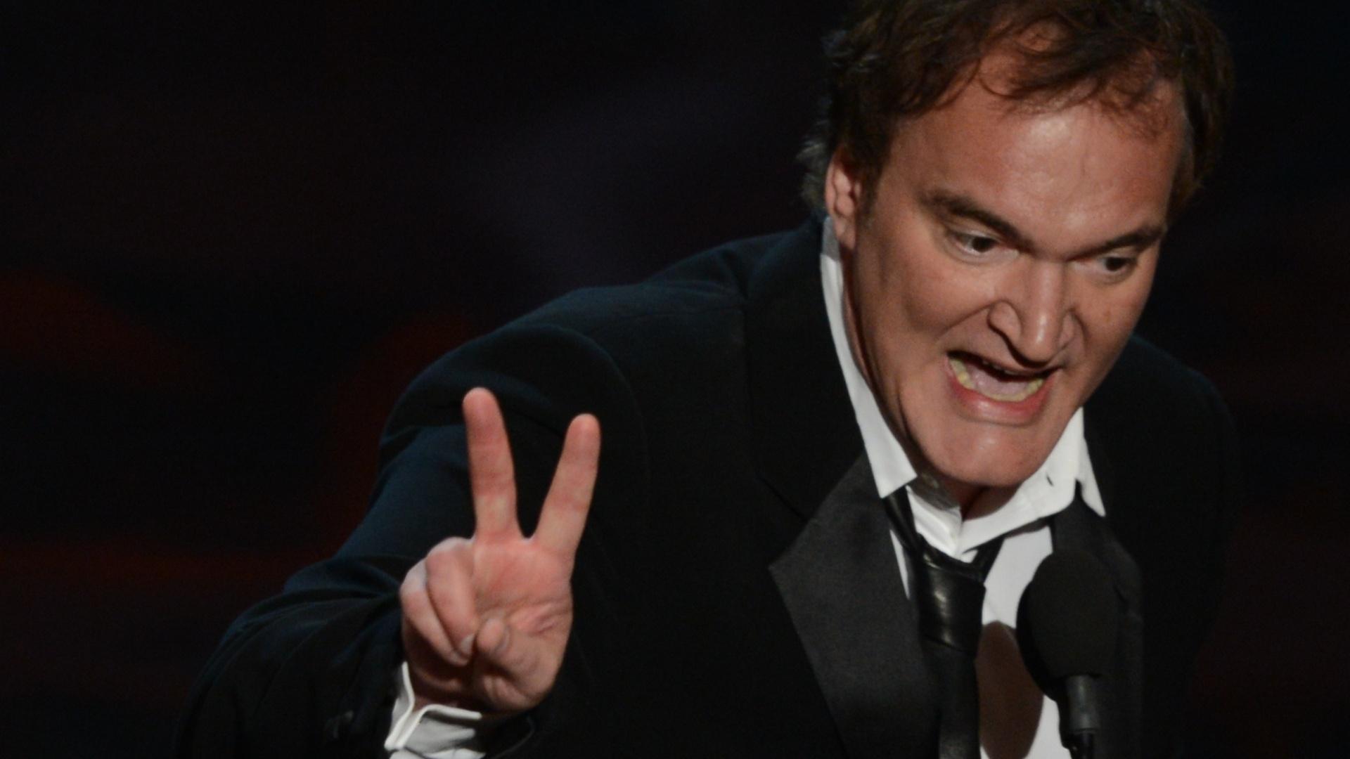 24.fev.2013 - Quentin Tarantino faz o sinal de paz ao receber o Oscar de melhor roteiro original por