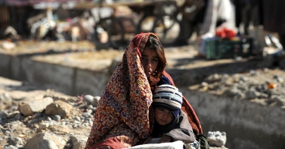 26.mar.2013 - Afegã segura criança enquanto espera táxi em rua de Candahar, no Afeganistão