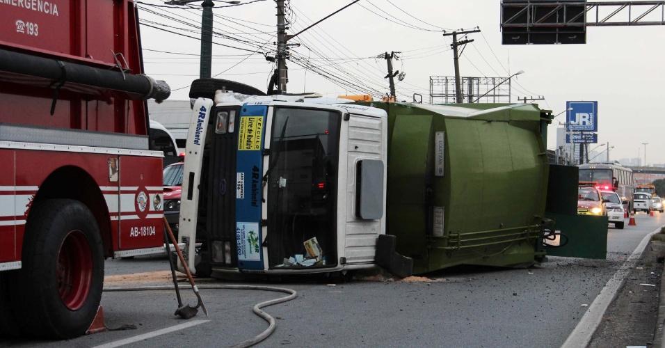 26.mar.2013 - Bombeiros, policiais e agentes de trânsito trabalham em área onde um caminhão de lixo tombou, no km 14,5 da rodovia Castello Branco, sentido interior, em São Paulo