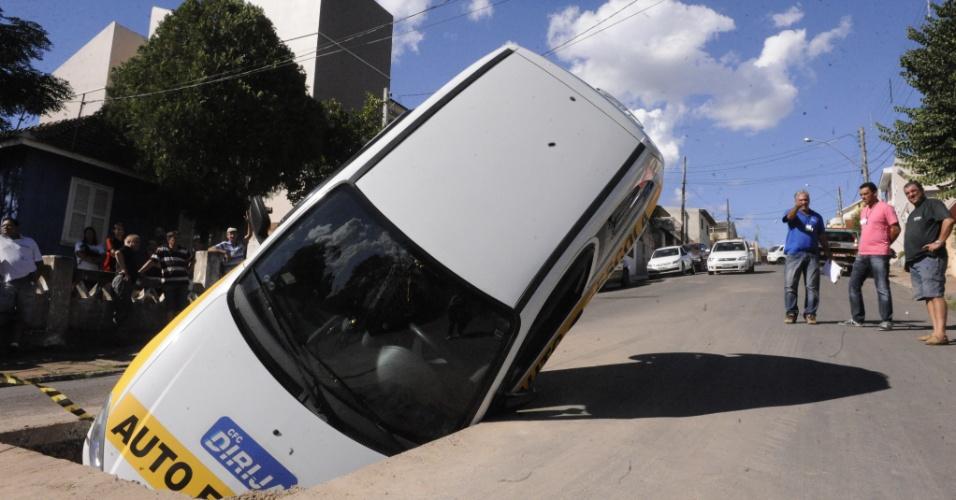 26.mar.2013 - Carro de autoescola caiu em buraco em Santa Maria (RS). Segundo uma testemunha, por volta das 15h o condutor do veículo teria desviado de duas crianças que andavam de bicicleta na rua e caído no buraco