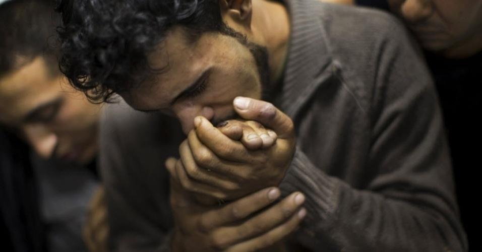 """26.mar.2013 - Esta imagem do fotógrafo Bernat Armangue, da agência de notícias """"Associated Press"""", foi eleita na segunda-feira (25) a Foto do Ano do 9º Concurso Internacional de Fotografia de Imprensa da China. A imagem, de novembro de 2012, retrata um palestino beijando a mão de um parente morto em um depósito de cadáveres de um hospital na Cidade de Gaza"""