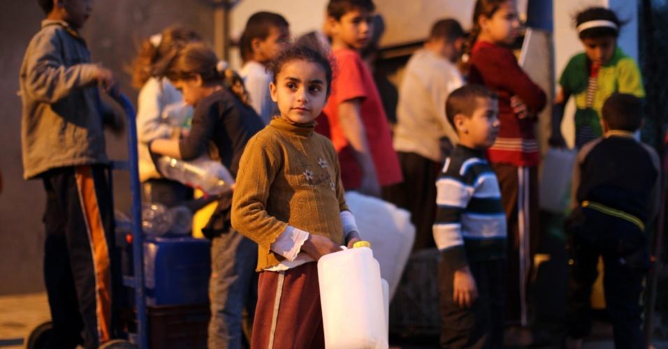 26.mar.2013 - Garotos e garotas palestinos fazem fila para encher recipientes de plástico com água no campo de refugiados Deir al-Balah, no centro da Faixa de Gaza