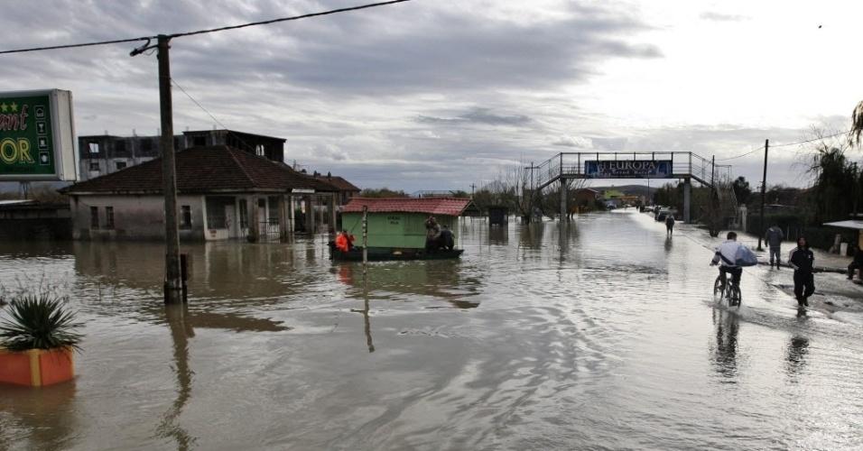 26.mar.2013 - Homem anda de bicicleta (direita) por rua inundada da região de Shkodër, na Albânia