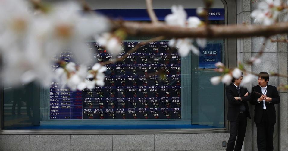 26.mar.2013 - Pessoas passam por rua florida na época do florescer das cerejeiras em Tóquio, no Japão