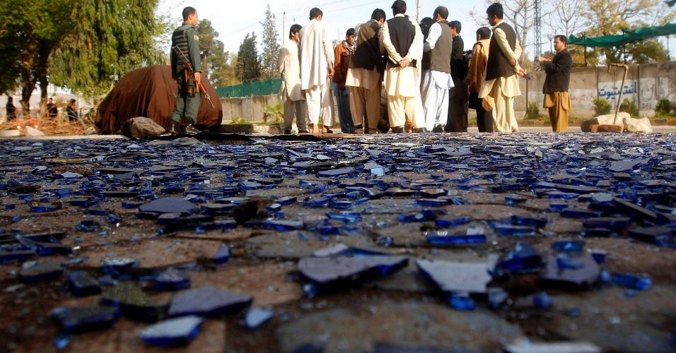 26.mar.2013 - Pessoas se reúnem próximo de cacos de vidro, quebrados por uma explosão a bomba em um ataque suicida em Jalalabad (Afeganistão). Três membros do taleban mataram cinco policiais no ataque, que coincide com a visita do secretário de Estado dos EUA, John Kerry