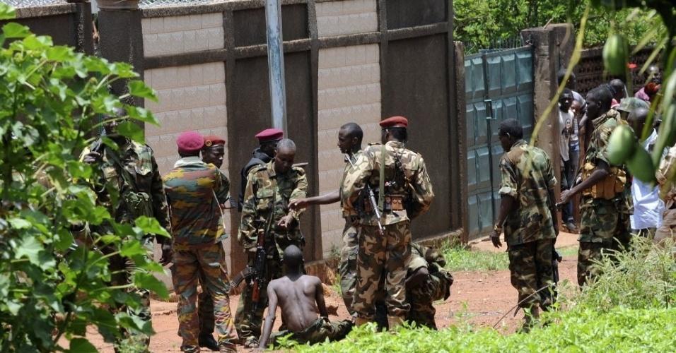 26.mar.2013 - Rebeldes da coalizão Seleka detêm homem usando trajes militares (centro, sentado) que estava assaltando uma casa no bairro de Bangui, na República Centro-Africana