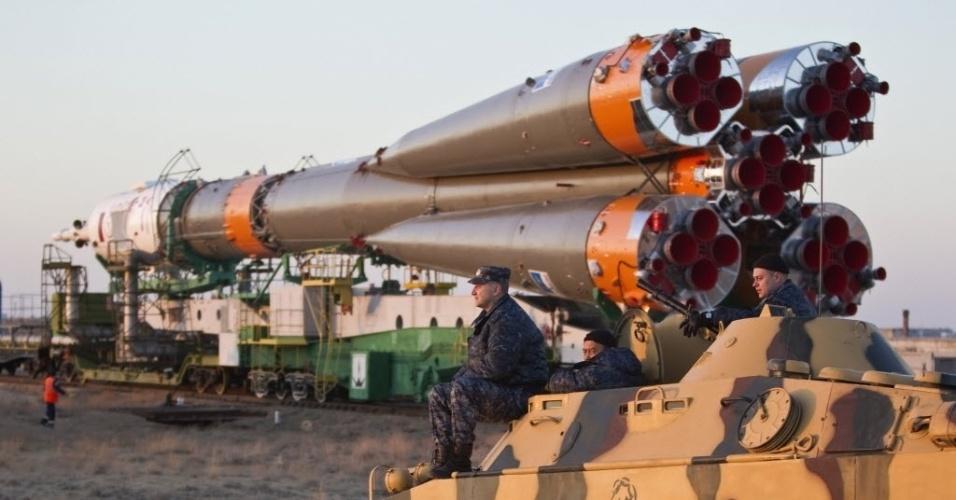 26.mar.2013 - Militares observam em cima de um tanque blindado e fazem a segurança do transporte da nave russa Soyuz até a plataforma de lançamento do cosmódromo de Baikonur, no Cazaquistão
