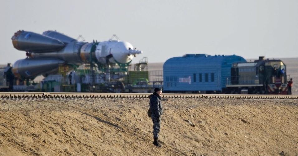 26.mar.2013 - Oficial vigia estrada de ferro usada para o transporte da nave Soyuz da base russa de montagem para a plataforma de lançamento do cosmódromo de Baikonur, no Cazaquistão