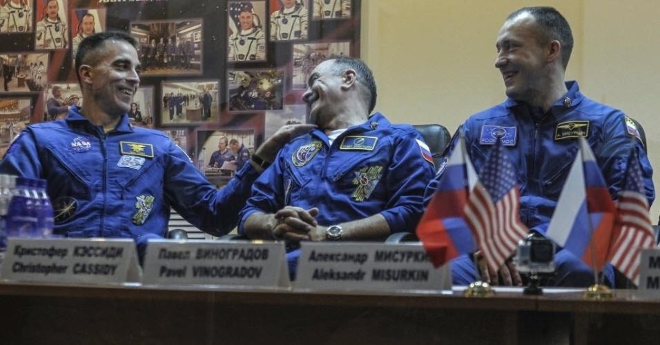 27.mar.2013 - O mecânico de voo Chris Cassidy (à esquerda), astronauta da Nasa (Agência Espacial Norte-Americana); o cosmonauta russo Pavel Vinogradov (centro), comandante da nave Soyuz; e o cosmonauta russo Alexander Misurkin (à direita) conversam com a imprensa sobre a nova missão da Estação Espacial Internacional (ISS, na sigla em inglês). O trio deverá chegar à plataforma nesta quinta-feira (28), após seis horas de voo na Soyuz