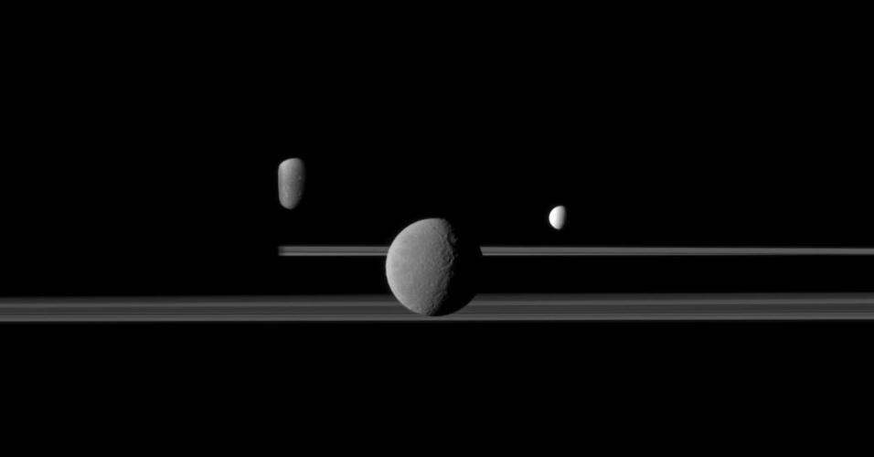 """27.mar.2013 - Três luas iluminam os anéis de Saturno, as duas """"longas faixas"""" que cortam a imagem, no lado escuro do planeta: Rhea (centro), Enceladus (à direita) e Dione (à esquerda), parcialmente ocultada por Saturno (sombra à esquerda)"""