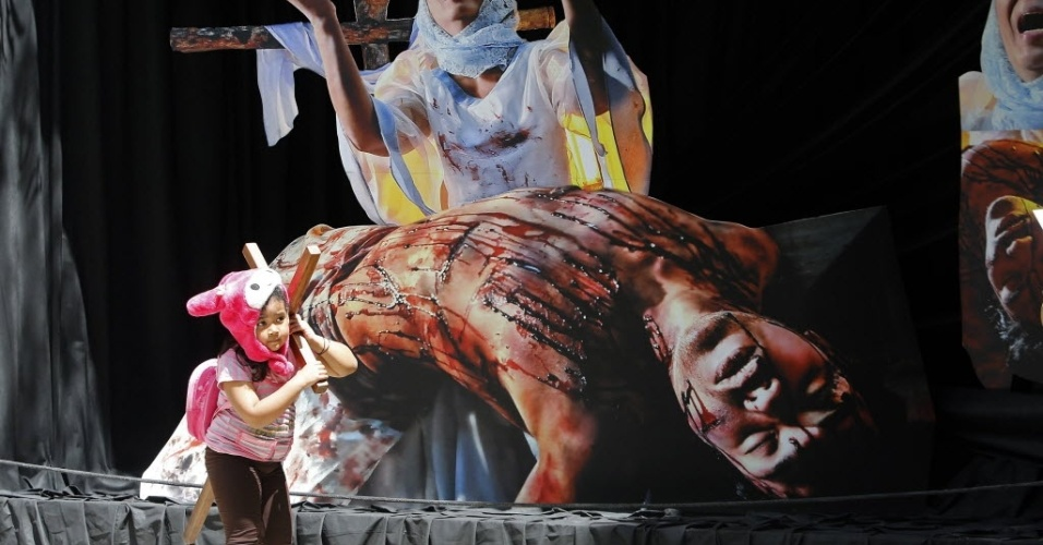 28.mar.2013 - Menina carrega cruz durante procissão em Manila (Filipinas)