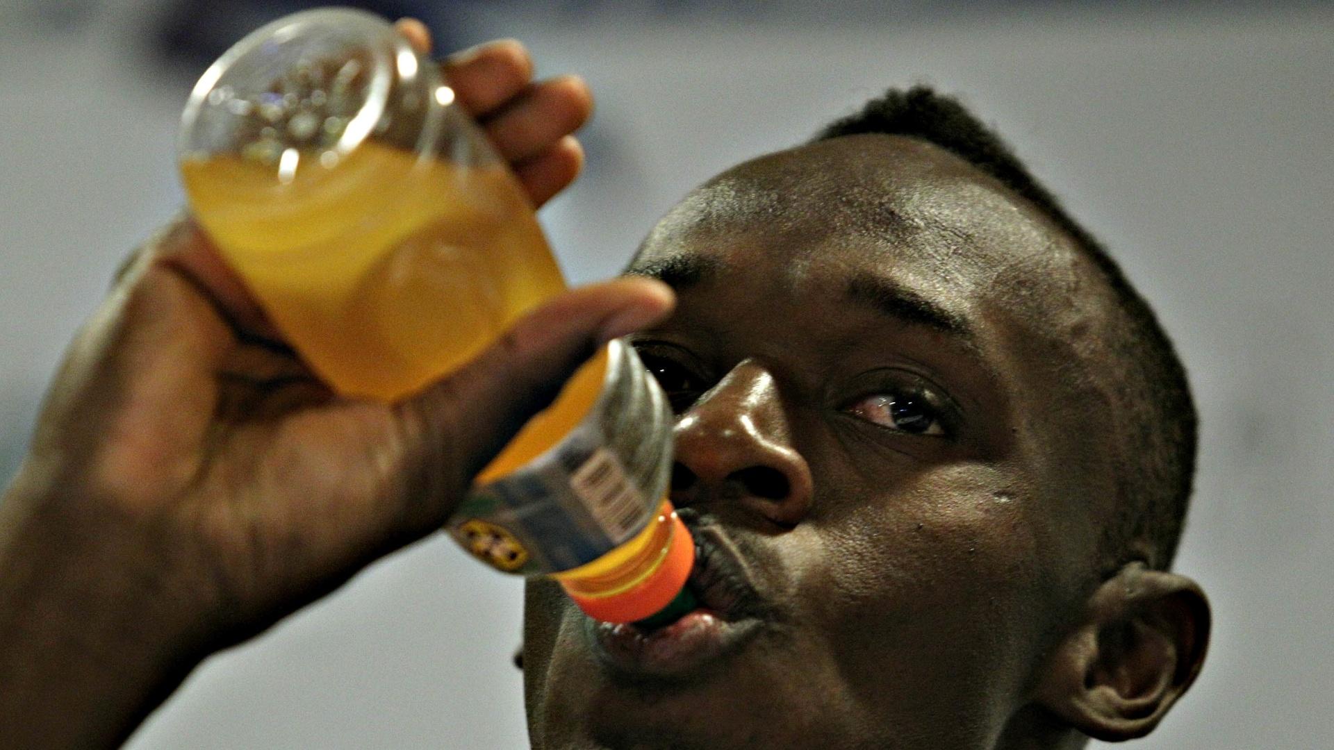 28.mar.2013 - Usain Bolt bebe isotônico de patrocinador durante coletiva no Rio de Janeiro, onde está para prova de 150 m, no próximo domingo, em Copacabana