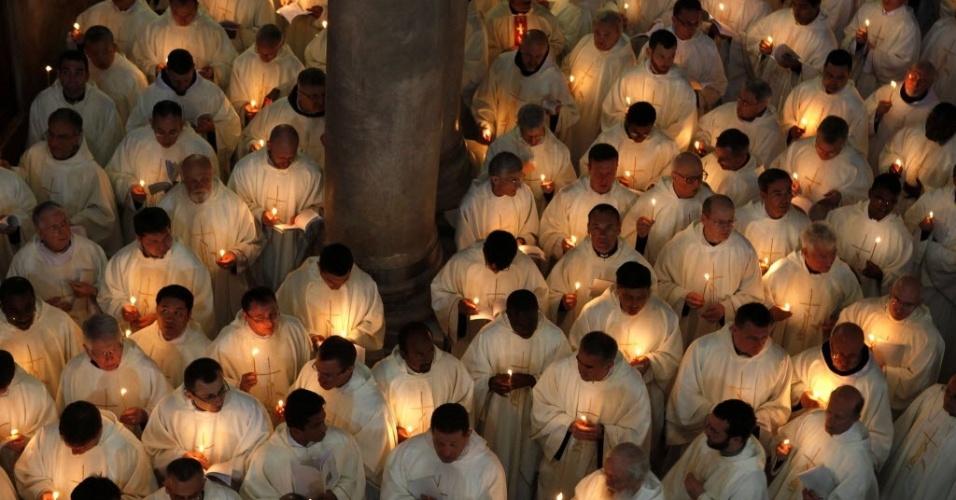 Clérigos católicos romanos seguram velas durante missa na igreja do Santo Sepulcro, em Jerusalém