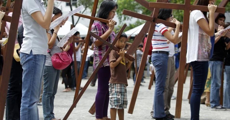 Menino carrega cruz junto com a sua família durante procissão em Manila (Filipinas)