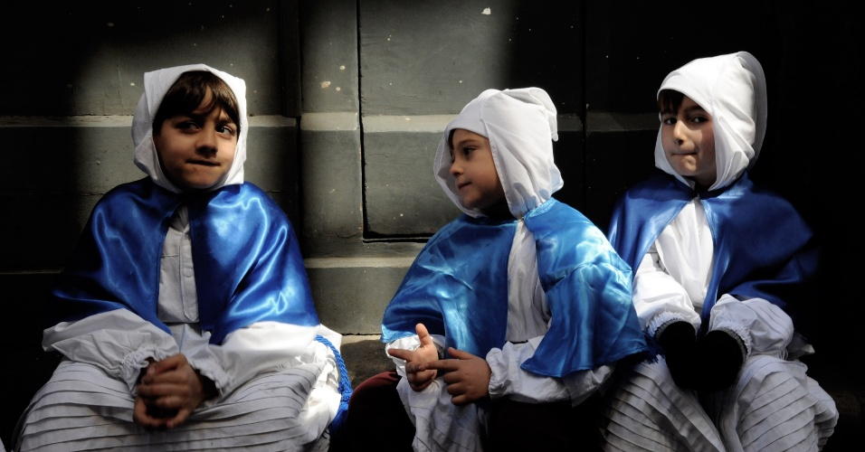 29.mar.2013 - Jovens penitentes descansam durante a procissão da Sexta-Feira Santa no sul da ilha de Procida, no golfo de Nápoles, Itália