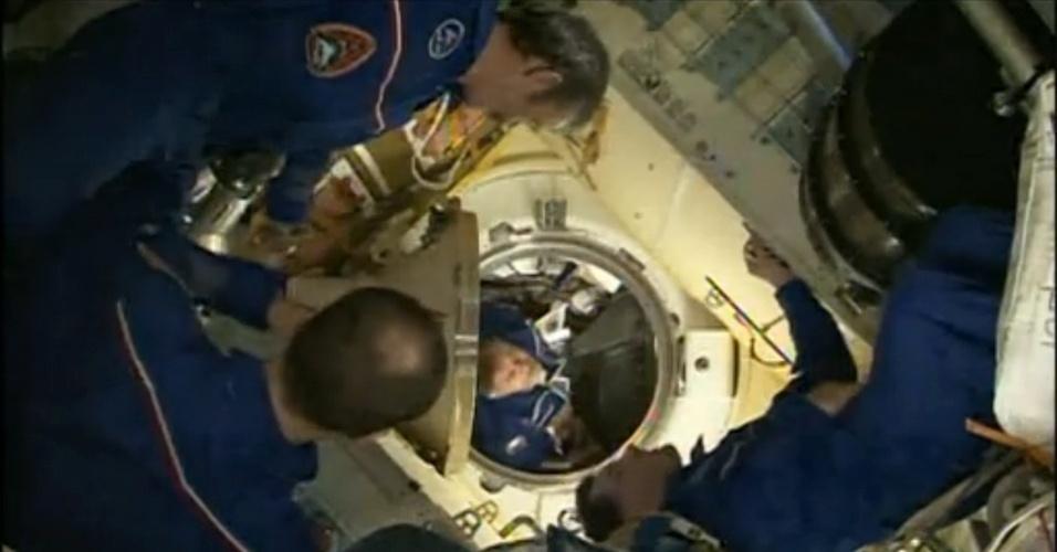 29.mar.2013 - O cosmonauta russo Pavel Vinogradov (fundo) abre a escotilha da Estação Espacial Internacional (ISS, na sigla em inglês) duas horas depois do acoplamento da nave russa Soyuz. Ele e sua equipe foram recebidos pelos atuais tripulantes da ISS: o canadense Chris Hadfield, chefe da atual missão 35, o russo Roman Romanenko e o norte-americano Tom Marshburn