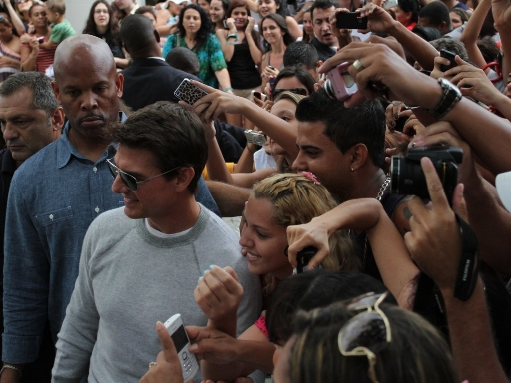 30.mar.2013 - Tom Cruise tira fotos com fs na porta do hotel em que est hospedado na zona sul do Rio. O ator est na cidade promovendo o filme 