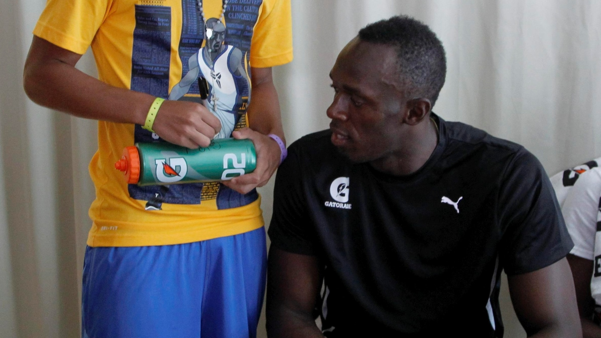 30.mar.2013 - Usain Bolt ganha autgrafo de Gabigol, jogador da base do Santos, depois de jogarem juntos futevlei em Copacabana: 