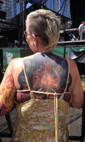 30.mar.2013: Eleonora Arantes mostra suas tatuagens nas costas. Ela está com o marido e, juntos, eles costuma ir a todos os festivais