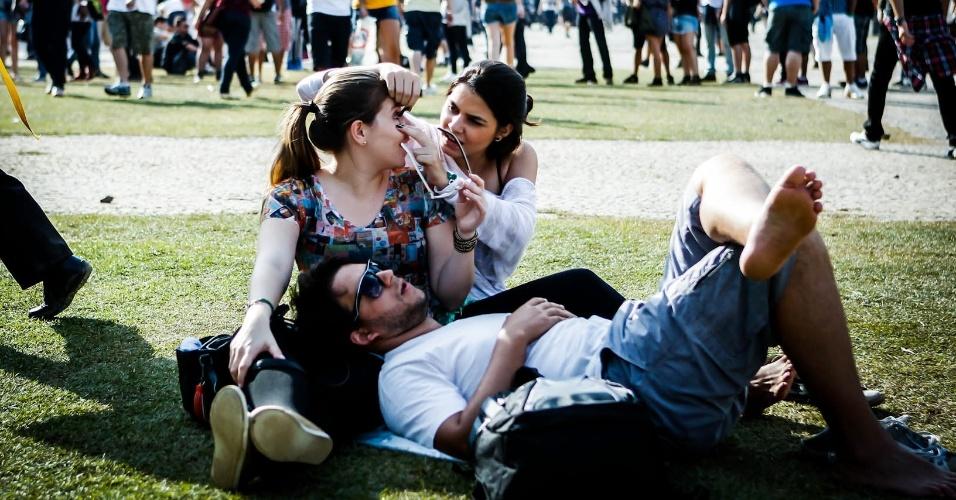 30.mar.2013: Garota maquia a amiga com rímel, enquanto descansam no gramado do Jockey