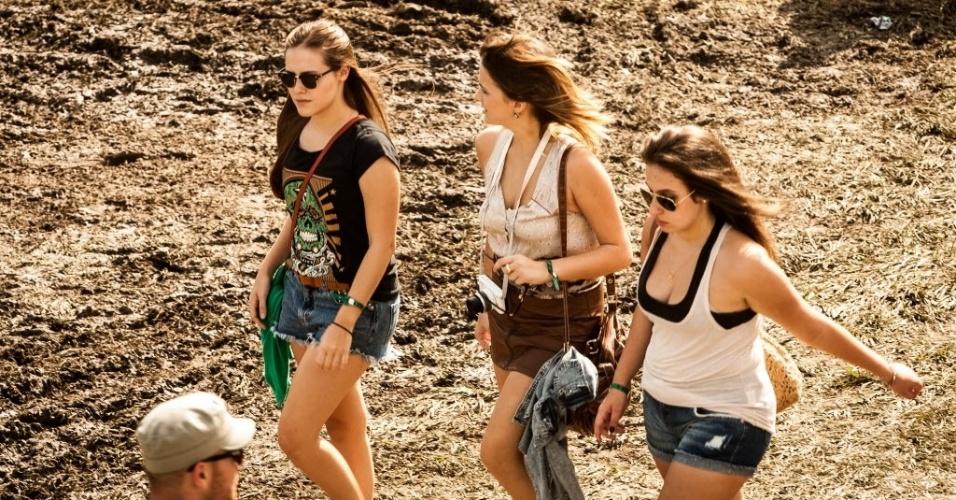 30.mar.2013: Garotas caminham em lama formada ontem, que diferentemente deste sábado, choveu durante a tarde