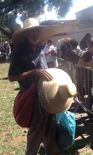 """30.mar.2013 - Roberto Verdugo, que vendia capa de chuva na sexta, está vendendo chapéu para se proteger do sol neste sábado: """"Precisa se adaptar ao clima, né?"""""""
