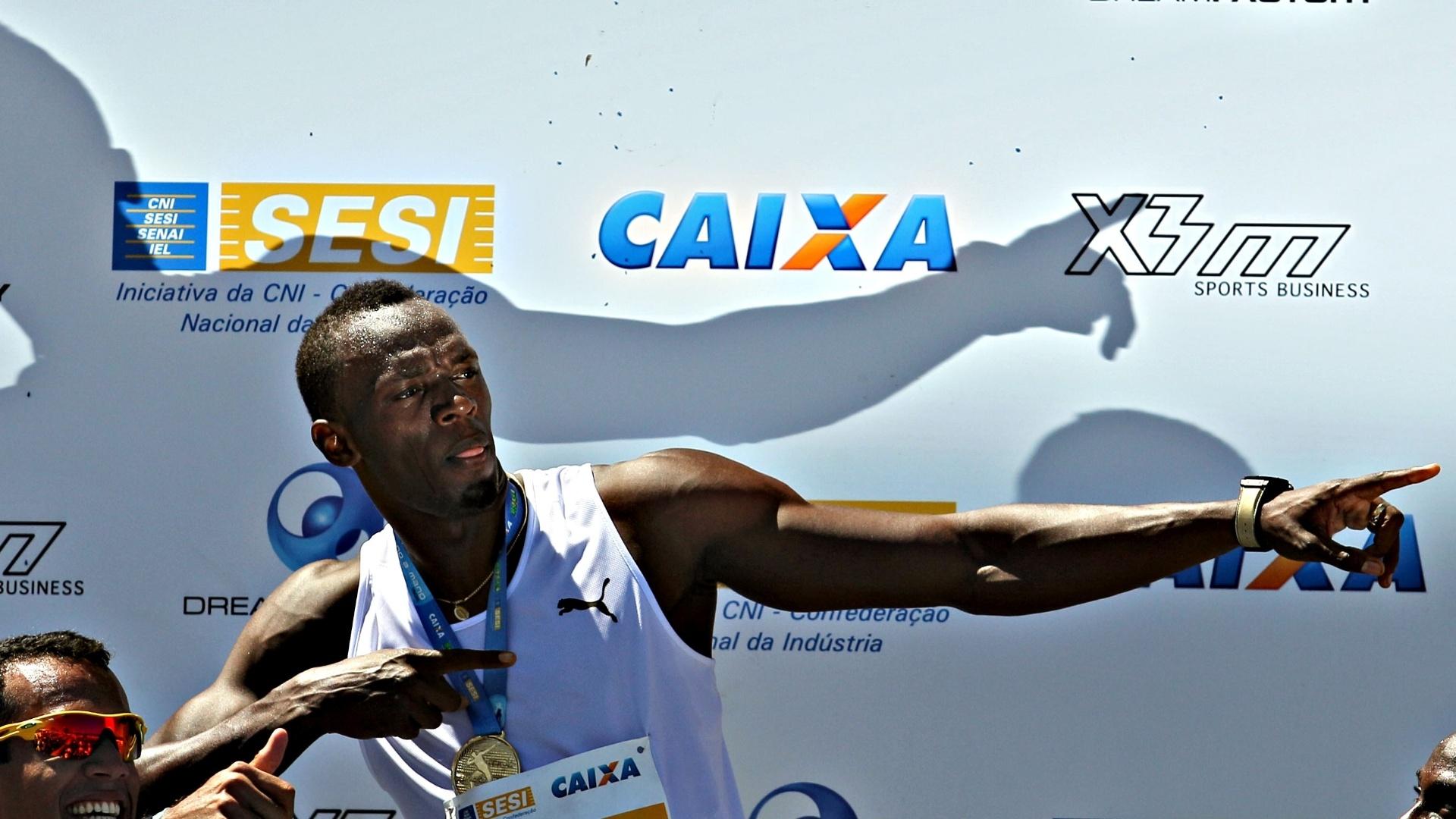 31.mar.2013 - Usain Bolt faz o seu famoso gesto após vencer desafio na praia de Copacabana