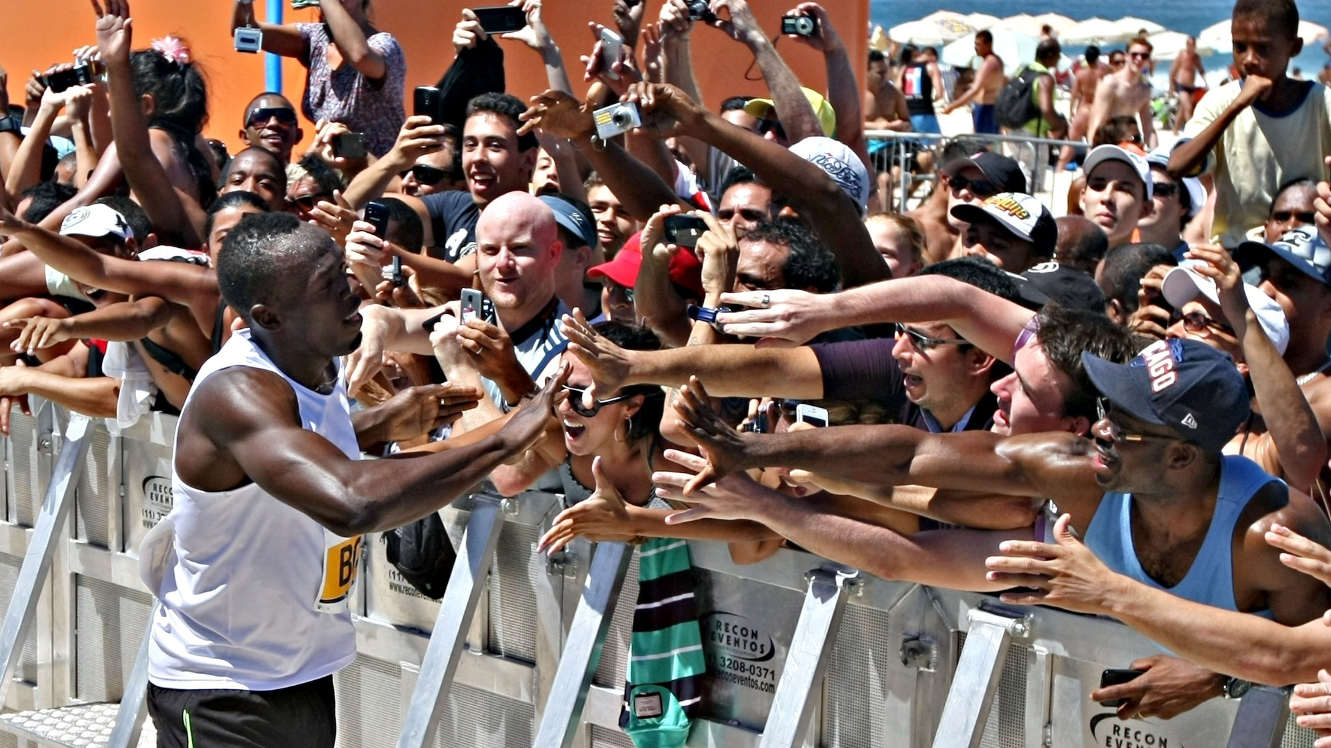 31.mar.2013 - Usain Bolt interage com os fs aps vencer desafio na praia de Copacabana