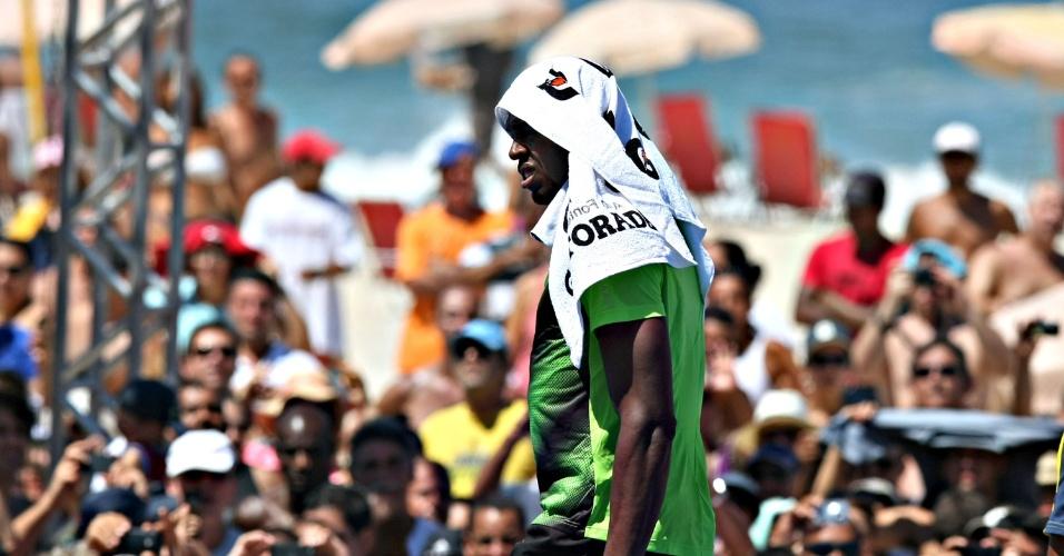 31.mar.2013 - Usain Bolt se protege do sol durante desafio na praia de Copacabana