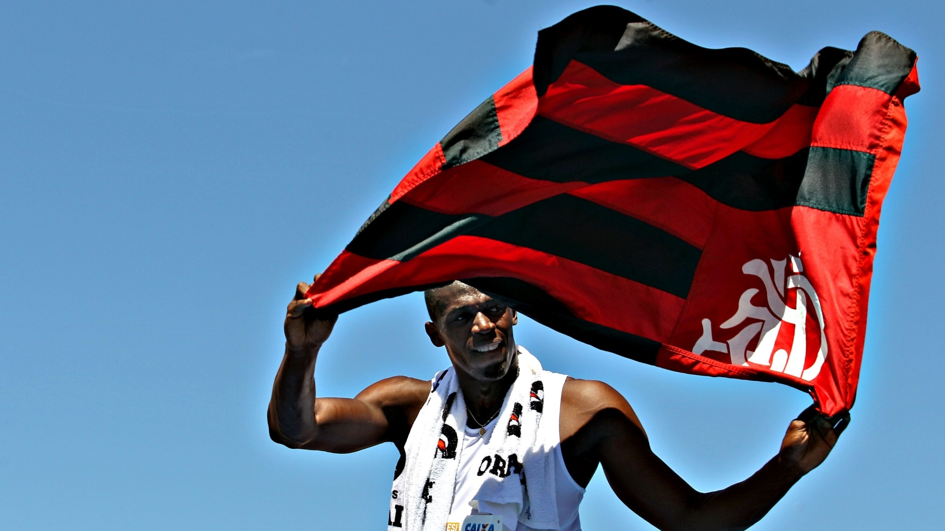 31.mar.2013 - Usain Bolt segura bandeira do Flamengo aps vencer desafio na praia de Copacabana