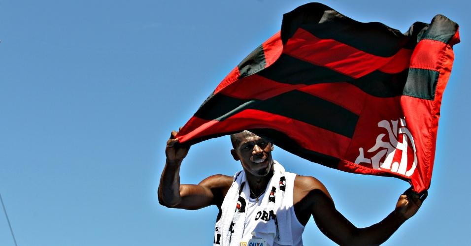 31.mar.2013 - Usain Bolt segura bandeira do Flamengo após vencer desafio na praia de Copacabana