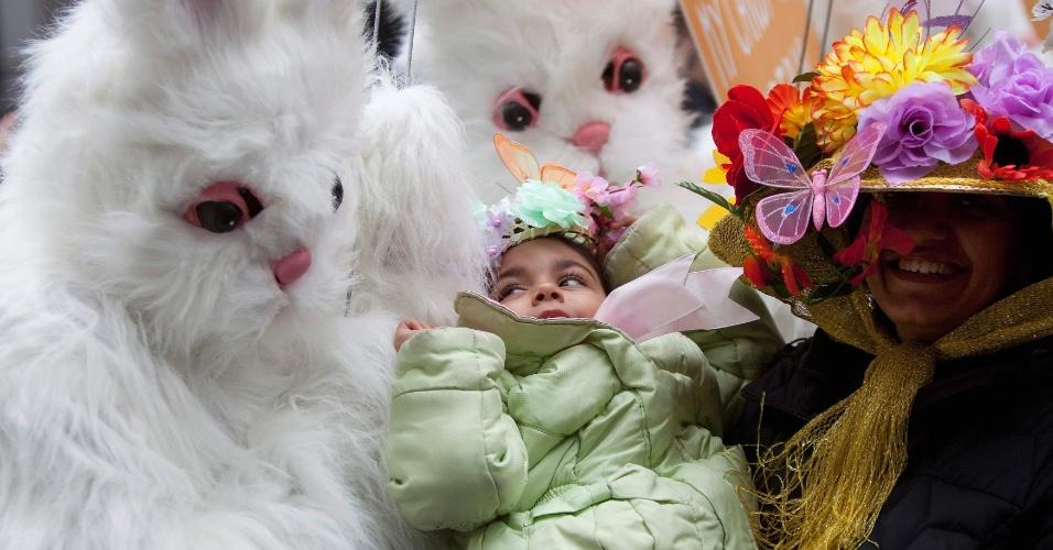 Criança observa pessoas fantasiadas de coelhos durante desfile de Páscoa em Nova York
