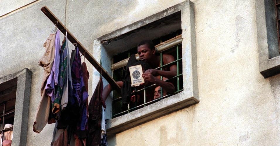 1º.abr.2013 - Detento do pavilhão 9 da Casa de Detenção mostra livro sobre direitos humanos