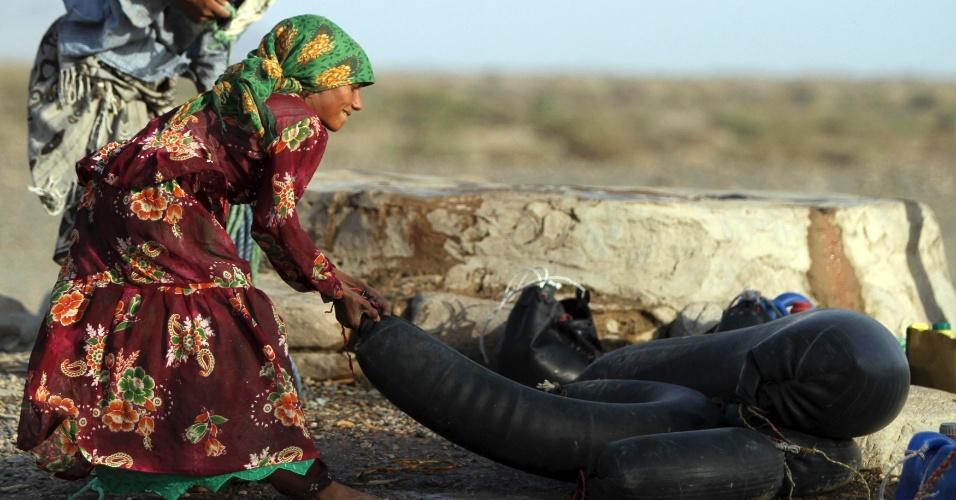 1º.abr.2013 - Mulher transporta água para consumo dentro da câmara de ar de um pneu, nesta segunda-feira (1º), no Iêmen