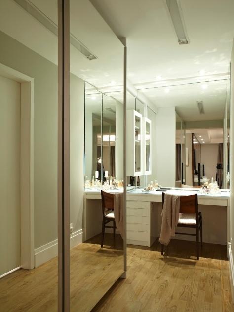 Mobiliado com armários desenvolvidos pelo escritório Selma de Sá, executados sob medida em marcenaria, o espaço (17,80 m²) também funciona como a antessala do banheiro. Espelhos revestem a parede e a maioria das portas de correr, enquanto os puxadores são barras de alumínio e as ferragens, Blum