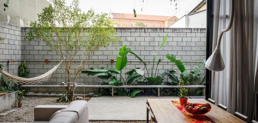 Tudo pode acontecer no jardim dos fundos, integrado à sala de estar e jantar da Casa Maracanã, projetada pelo escritório Terra e Tuma: as crianças aproveitam para brincar no quintal, os adultos relaxam na rede e o bancão de concreto, que tem sua rigidez quebrada pelas plantas, pode acomodar os amigos