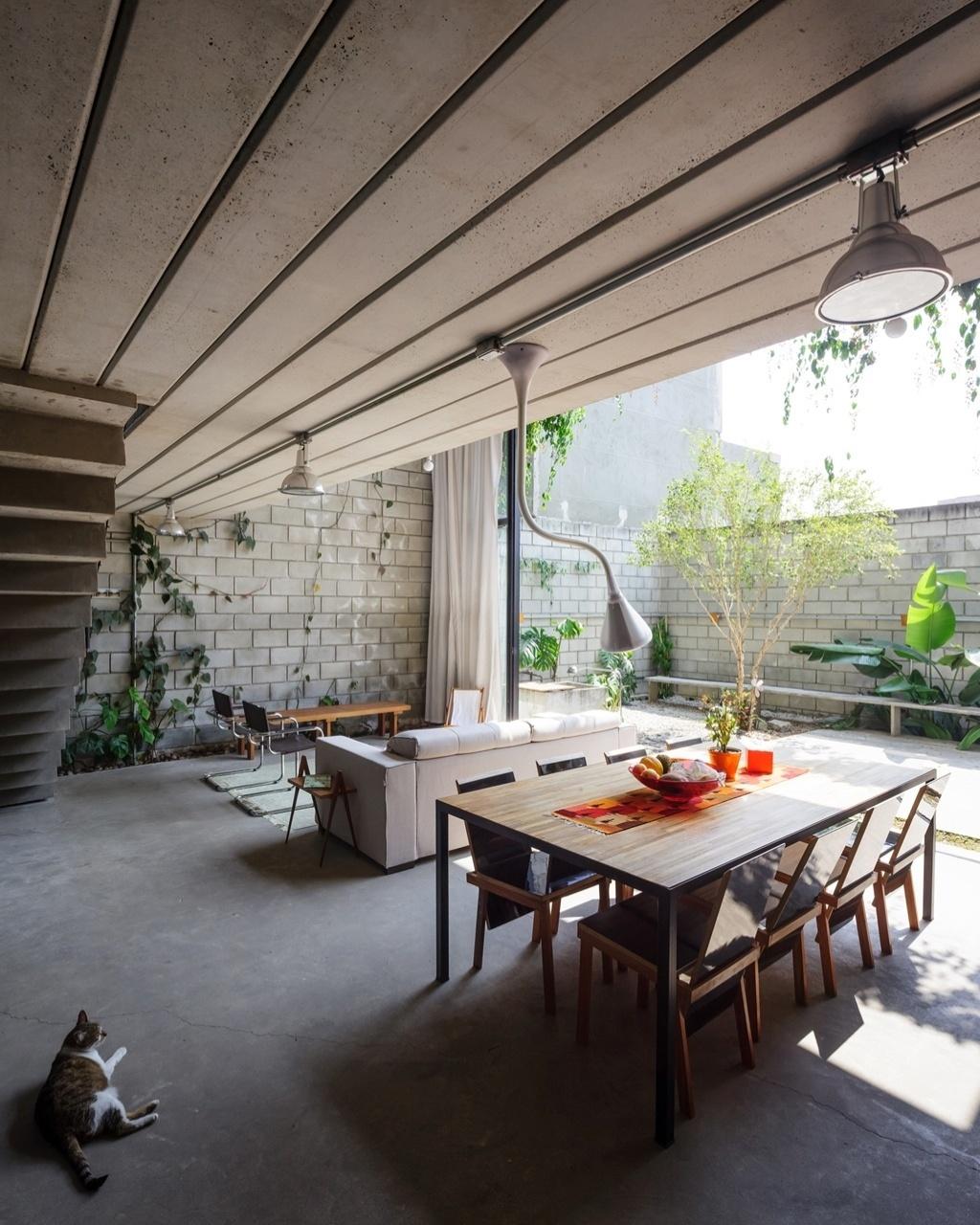 A área social que acomoda as salas de estar e jantar é totalmente aberta para o jardim. A laje maciça em concreto aparente recebeu trilho com luminária pendente e spots. A Casa Maracanã foi projetada pelo escritório Terra e Tuma