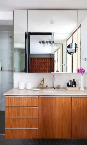 No banheiro, o box tem piso revestido por pastilhas cinza, enquanto a totalidade das paredes é recoberta por cerâmica branca brilhante com aspecto retrô. Sobre a bancada, o espelho generoso. A reforma do imóvel foi assinada pelo arquiteto Maurício Arruda