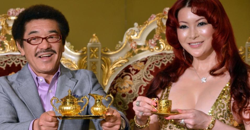3.abr.2013 - A japonesa Mika Kano (na direita) e o ex-campeão mundial de boxe Yoko Gushiken exibem conjunto de xícara e pires, avaliado em US$ 75 mil, e bandeja com açucareiro e jarra, avaliados em US$ 172 mil, todas feitas em ouro, na ?Expo Ouro? que acontece em Tóquio, nesta quarta-feira (3). A exposição pretende vender um total de US$ 130 milhões em produtos feitos de ouro, incluindo uma barra de ouro 120 kg cujo preço é de US$ 6,5 milhões