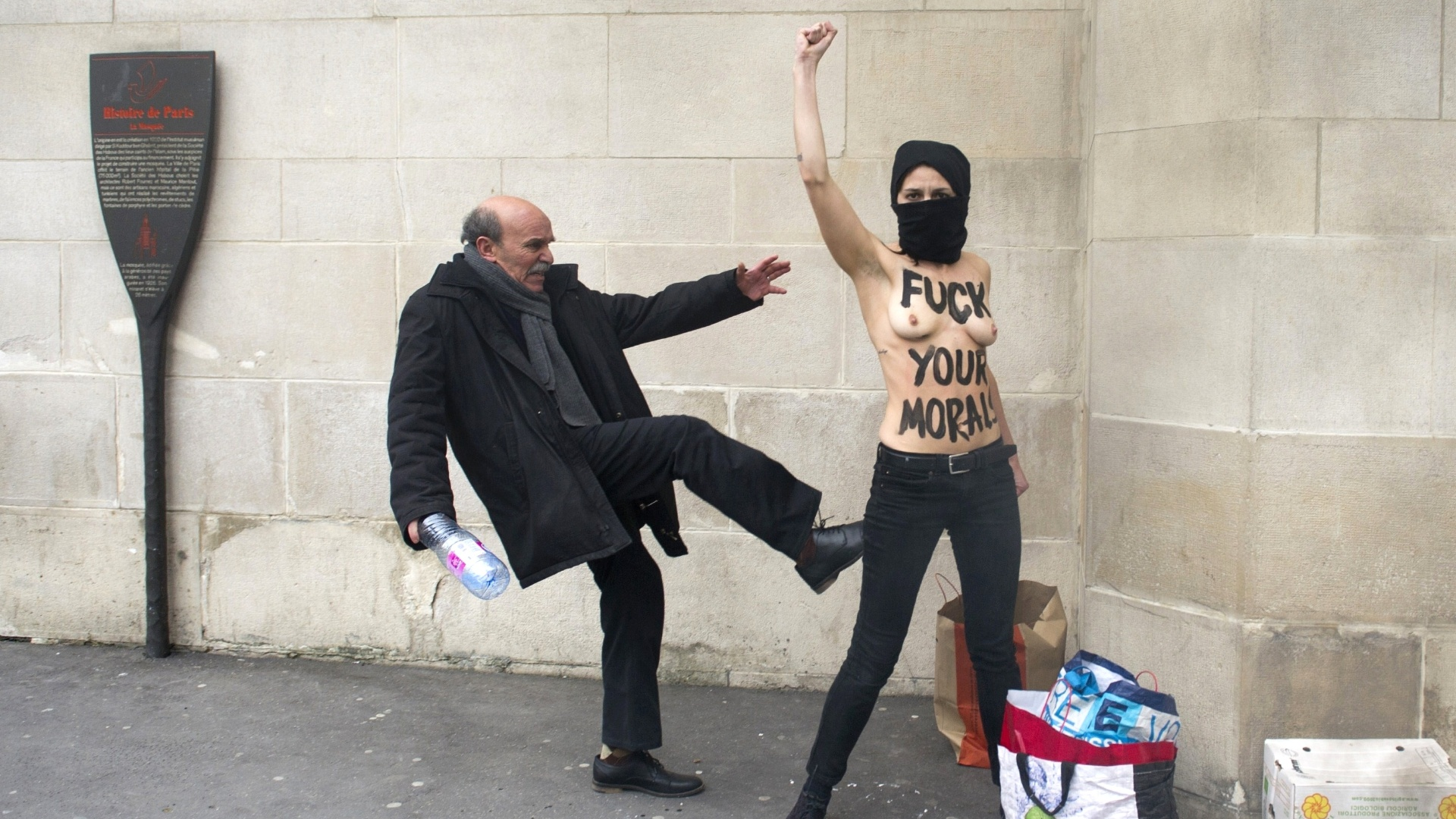 3.abr.2013 - Homem chuta uma ativista do Femen, grupo de origem ucraniana famoso por realizar protestos com o uso de topless, em protesto realizado em frente a mesquita em Paris nesta quarta-feira (3)