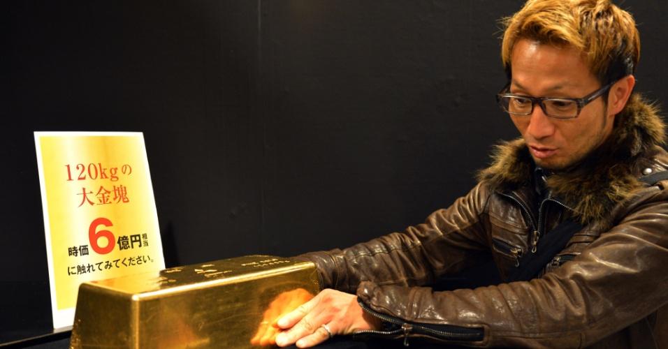 """3.abr.2013 - Homem observa barra de ouro de 120 kg, cujo preço é de R$ 13 milhões, que faz parte do acervo da """"Expo Ouro"""". A exposição, que acontece nesta quarta-feira, em Tóquio, pretende vender um total de R$ 263 milhões em produtos feitos de ouro"""